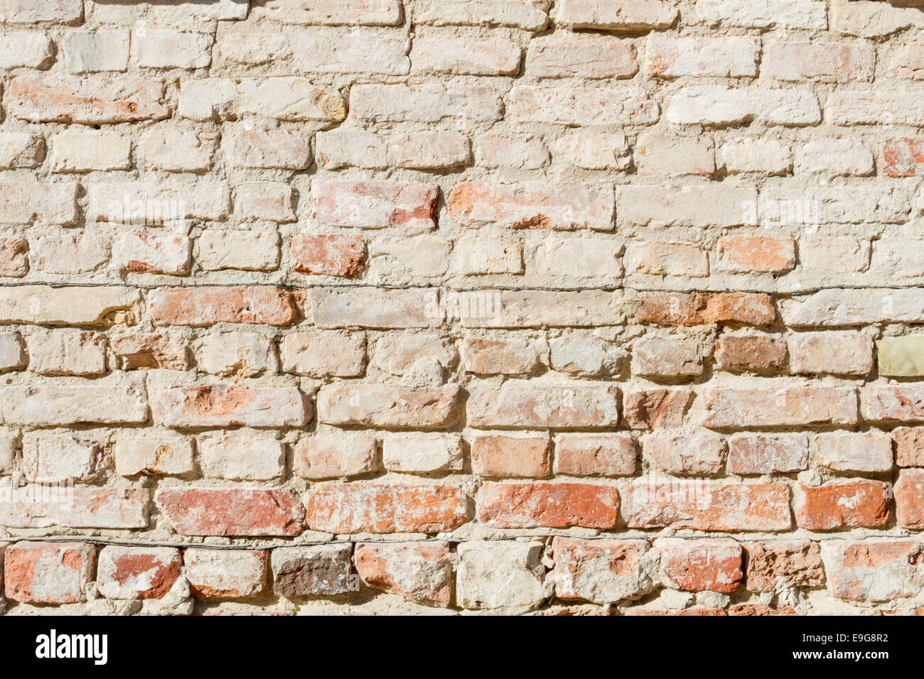 Bedraggled brick wall in dusted yellow - Stock Image