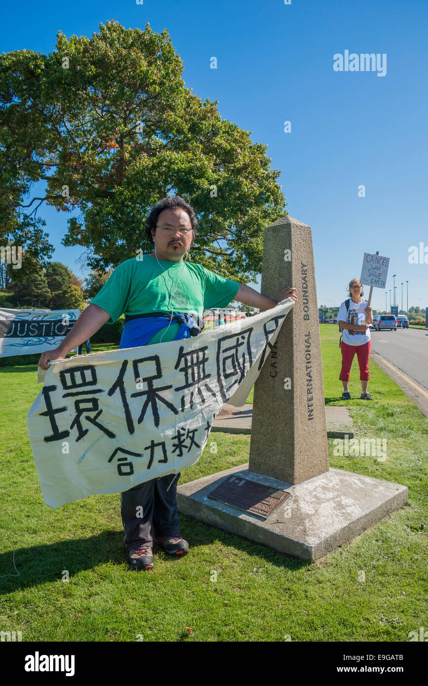 Climate Change protesters at Peace Arch U.S Canada border crossing. - Stock Image