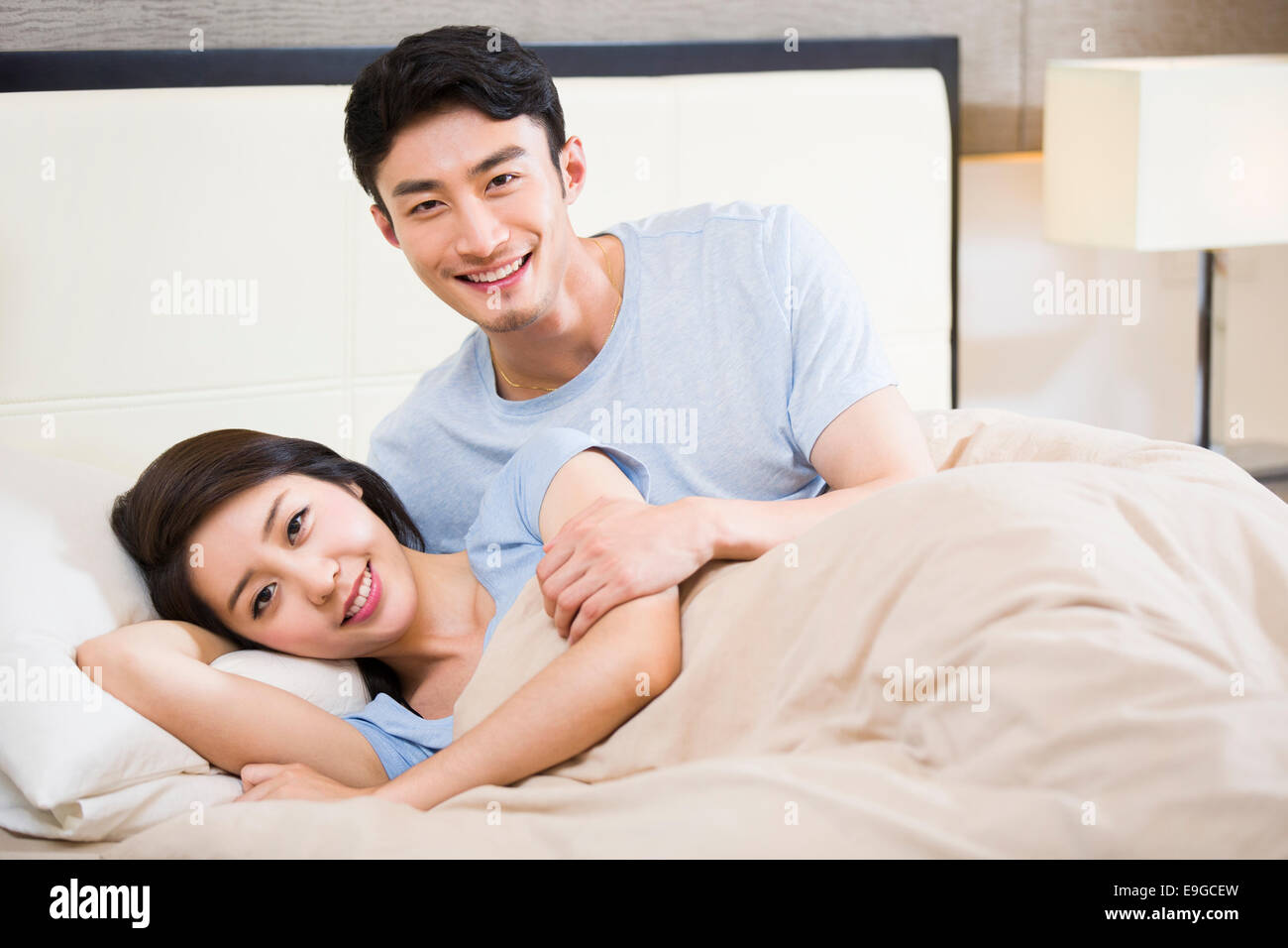 Young couple lying on bed - Stock Image