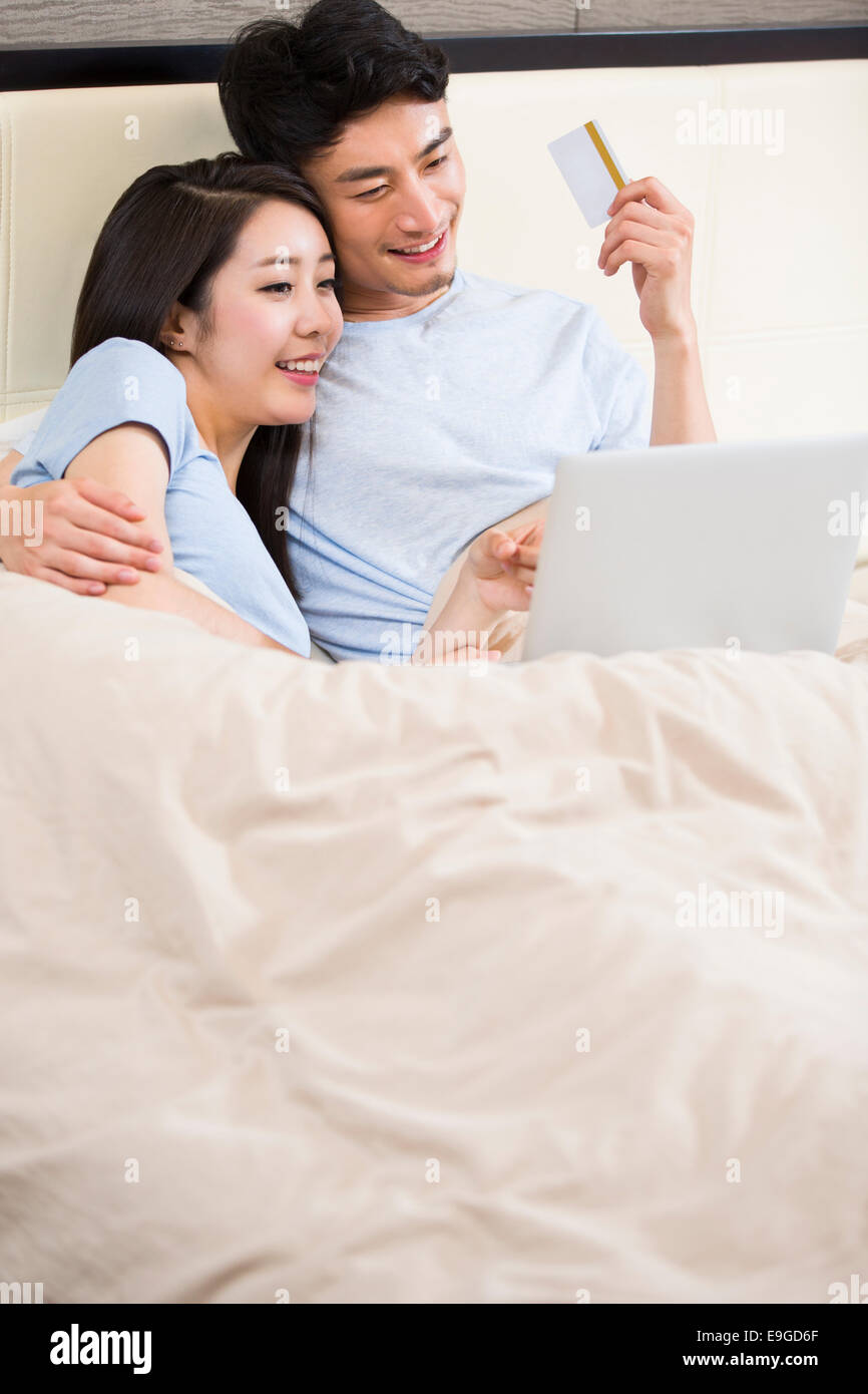 Young couple shopping online with laptop - Stock Image