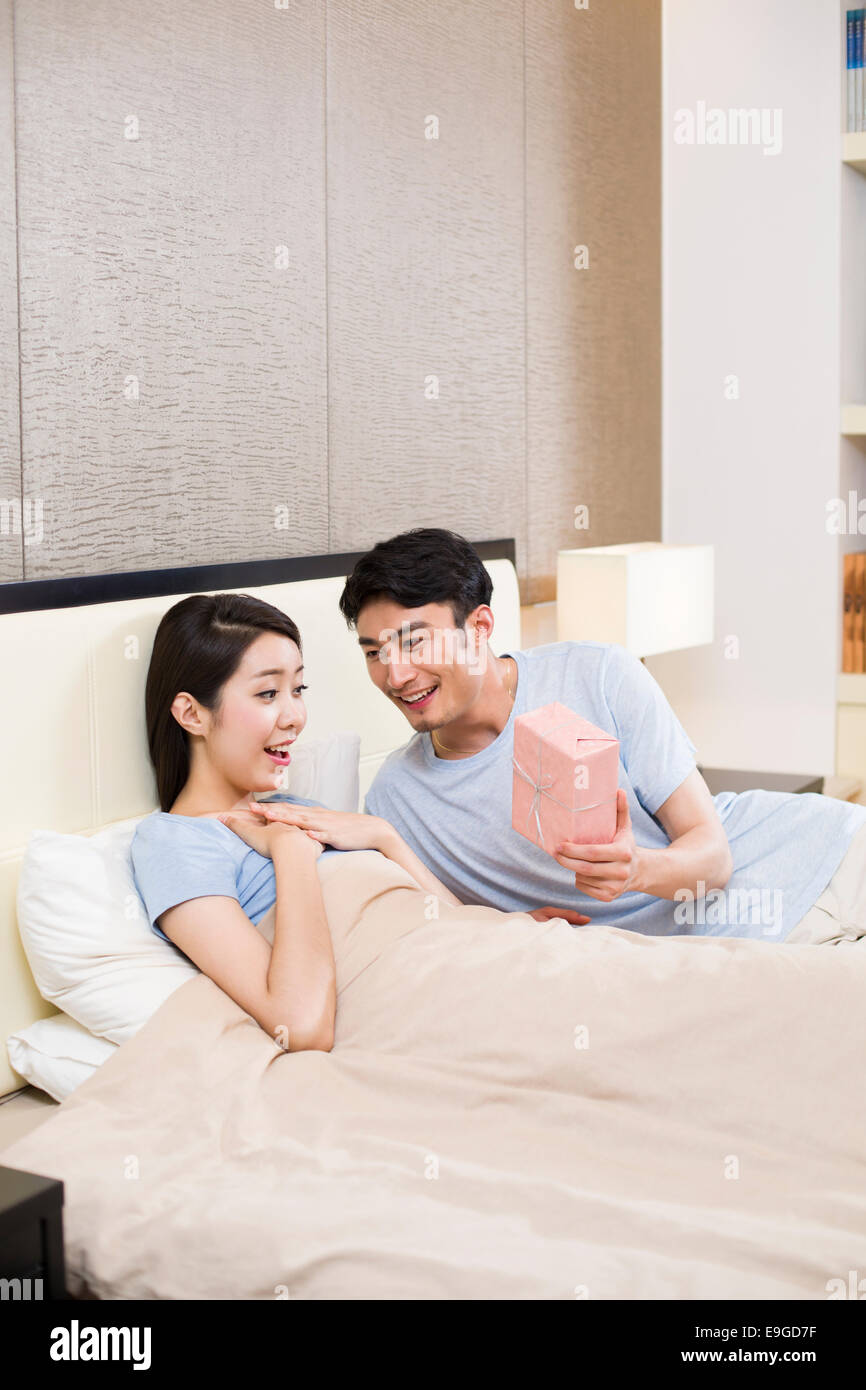 Surprised woman receiving gift from man - Stock Image