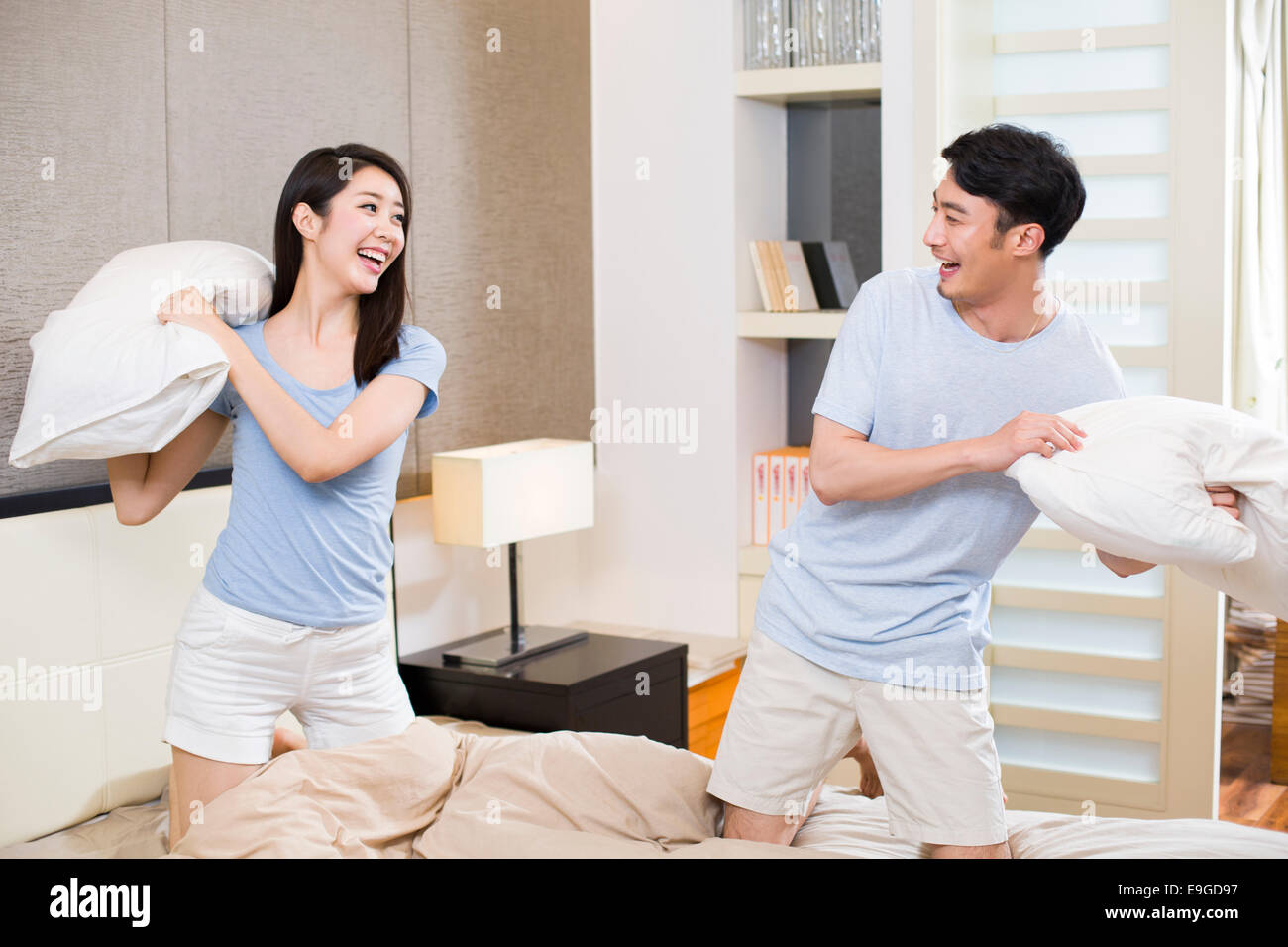 Young couple pillow fighting in bedroom - Stock Image