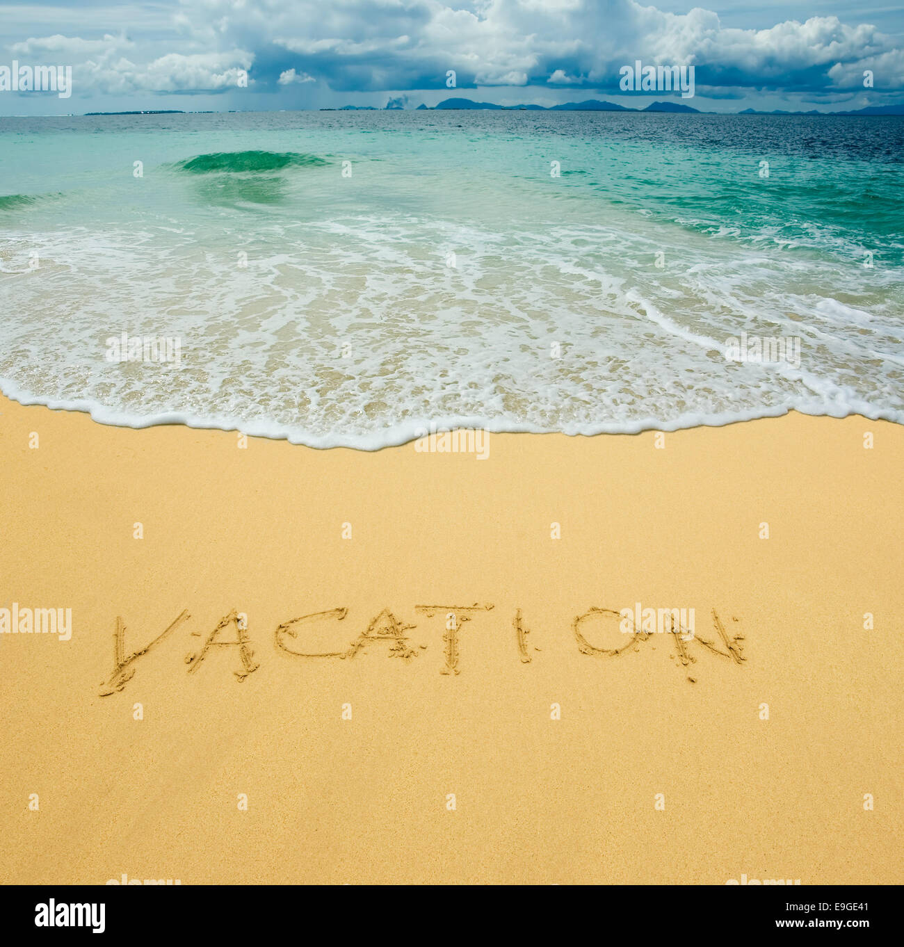 vacation written in a sandy tropical beach - Stock Image