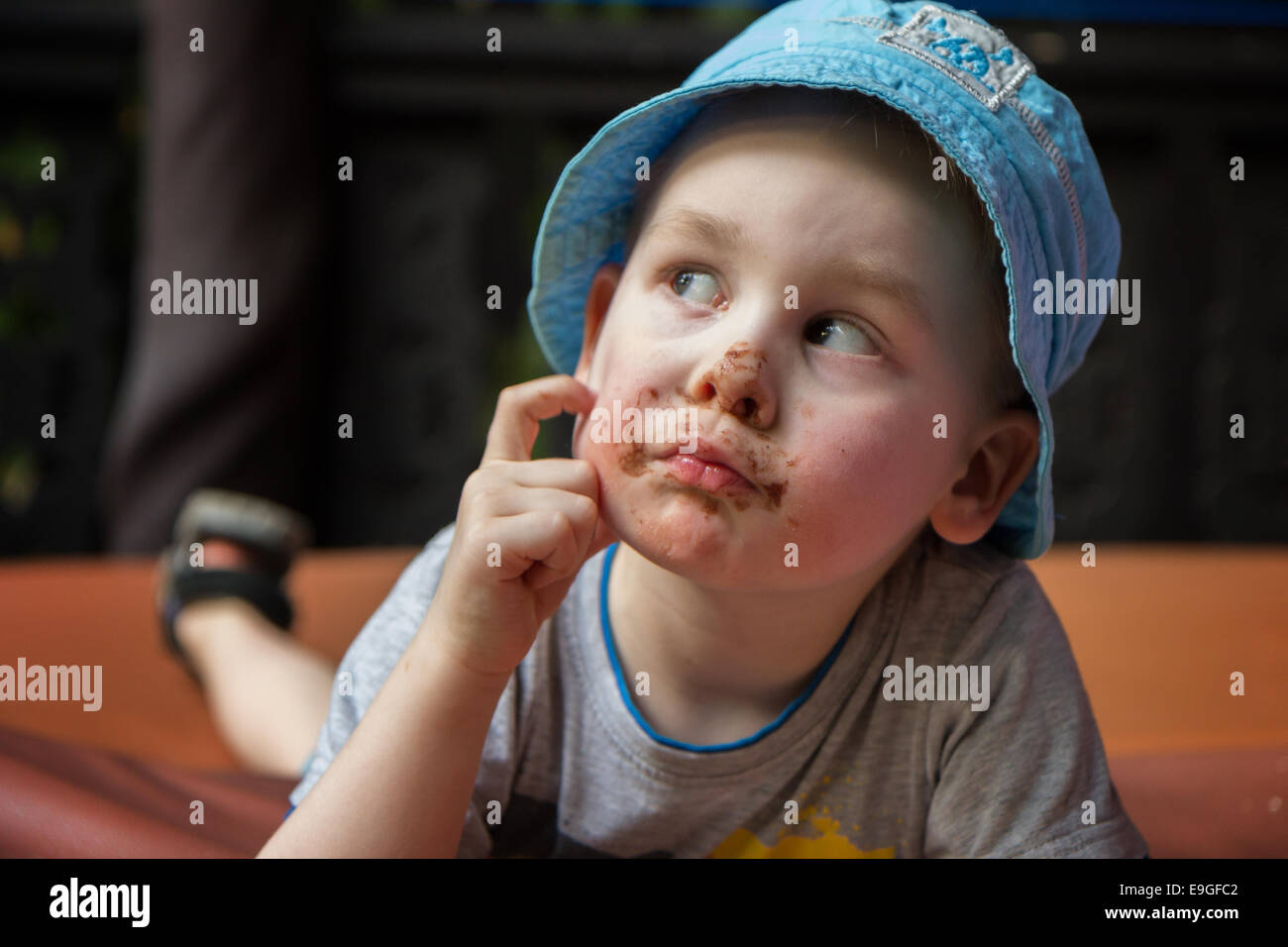 Closeup of a small boy pondering, face smudged with chocolate - Stock Image