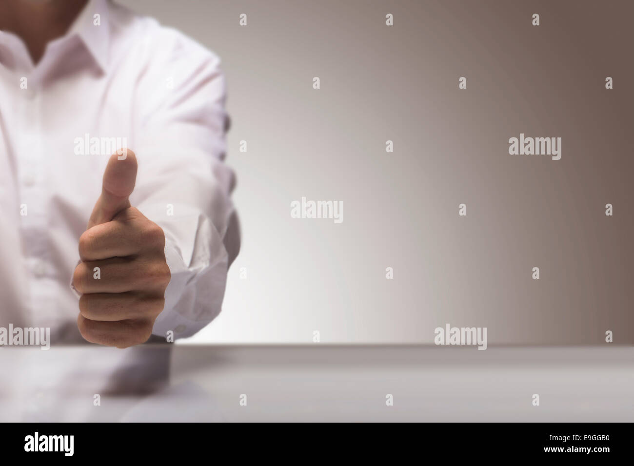 Man with one thumb up at the background of a glossy table and copy space on the right, concept image for illustration - Stock Image