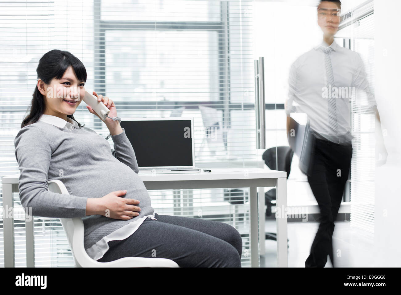 Pregnant businesswoman on the phone and businessman walking out - Stock Image