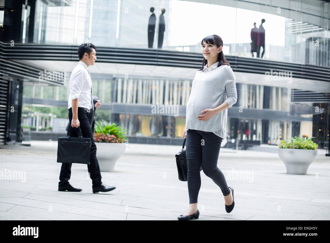Pregnant businesswoman walking in city center - Stock Image