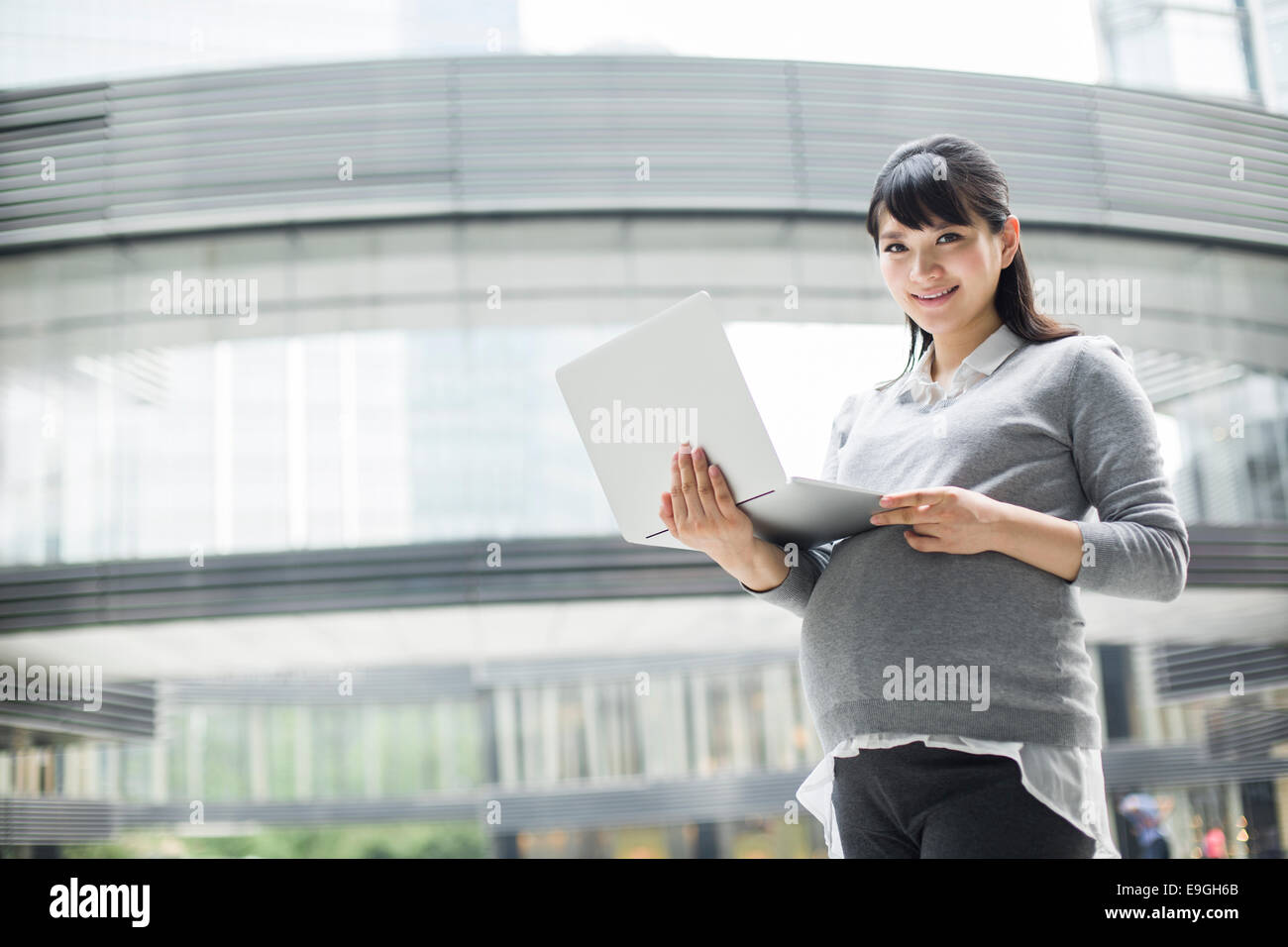 Pregnant businesswoman holding laptop Stock Photo