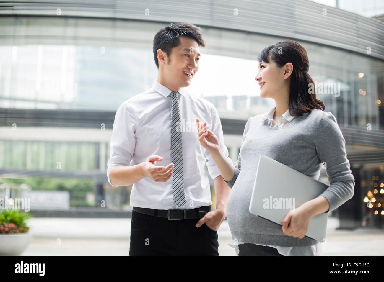 Pregnant businesswoman talking with colleague - Stock Image