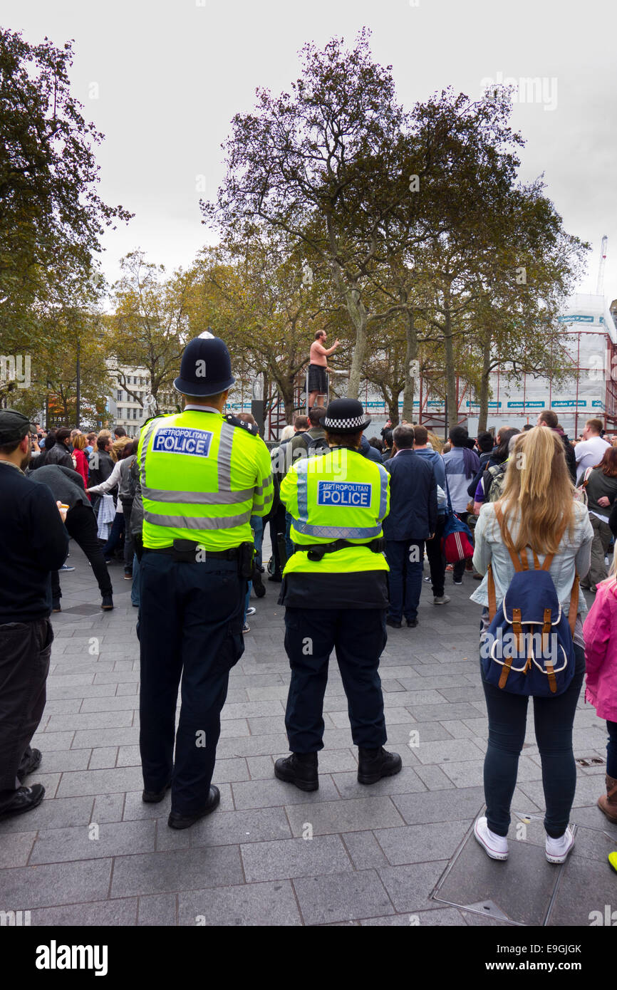 Street performer busker being watched by police in Leicester Square - Stock Image