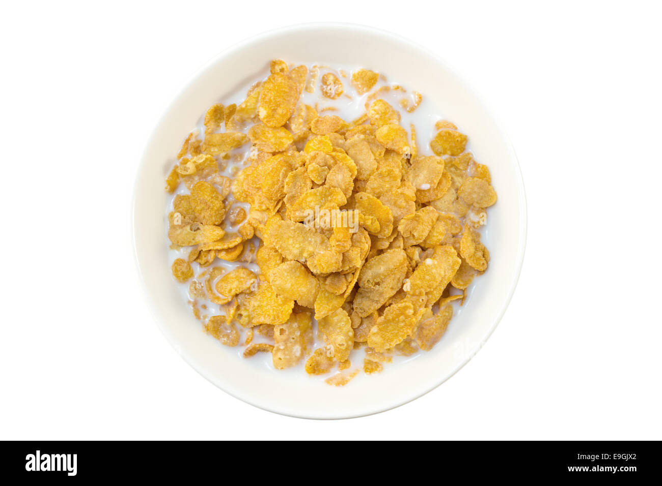 Closeup of corn flakes and milk in a bowl viewed from above, isolated on white background - Stock Image