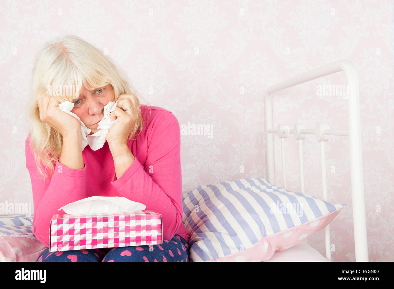 Sad woman with pink pyjama and tissues sitting on edge of bed - Stock Image