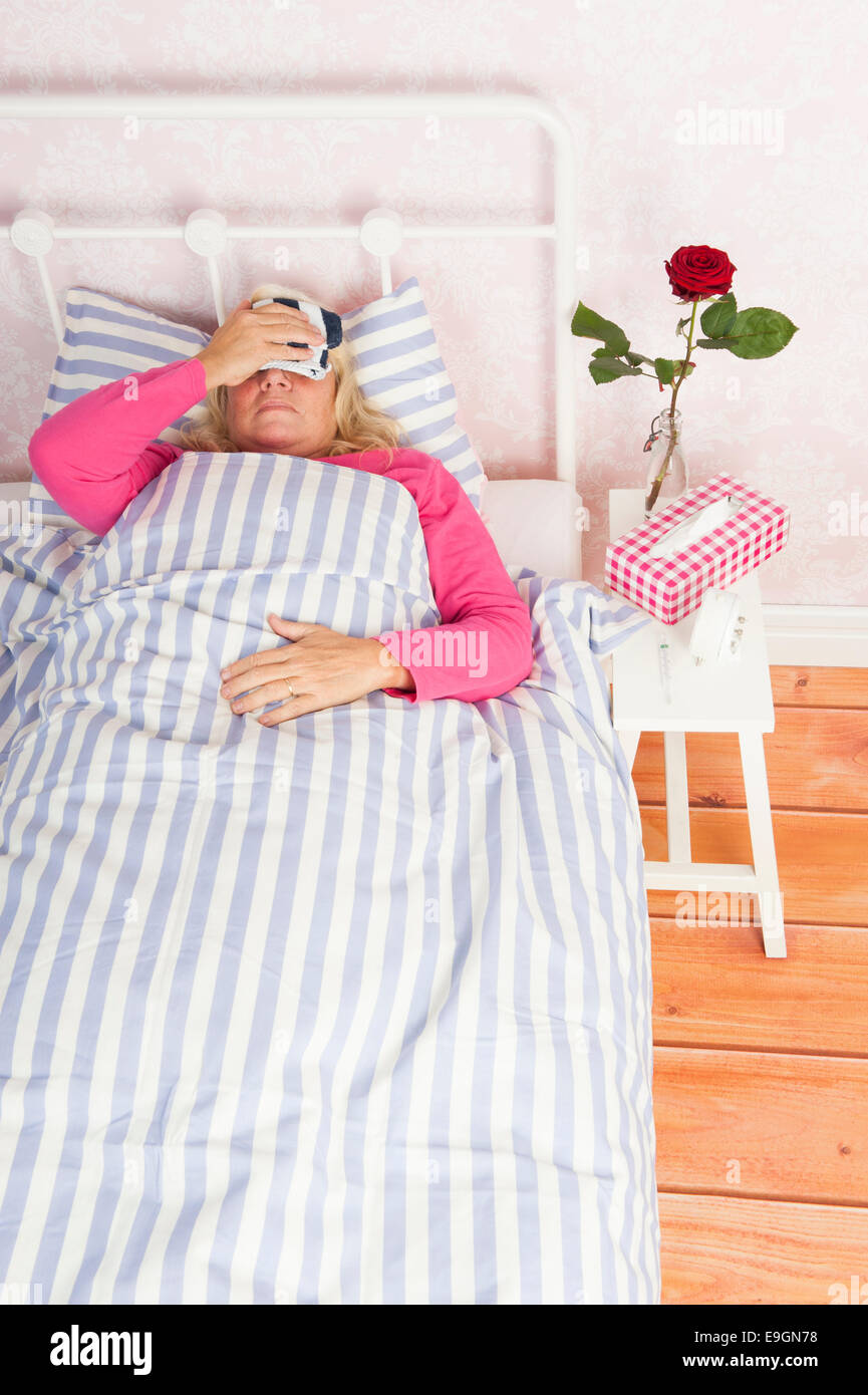 Sick woman in pink pajama with migraine, tissues and a rose lying in bed with washcloth - Stock Image