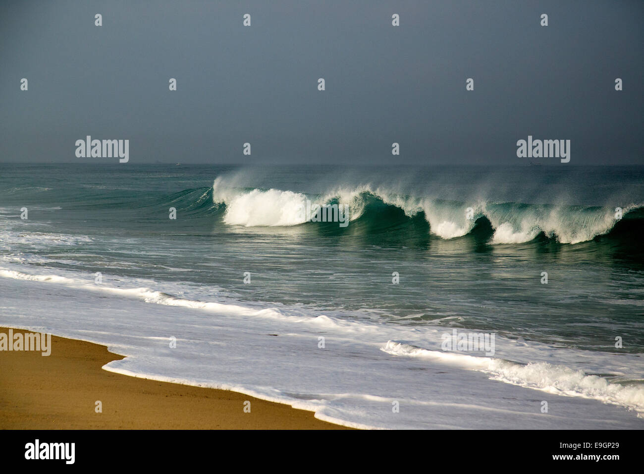 Wave breaking on beach shore. - Stock Image