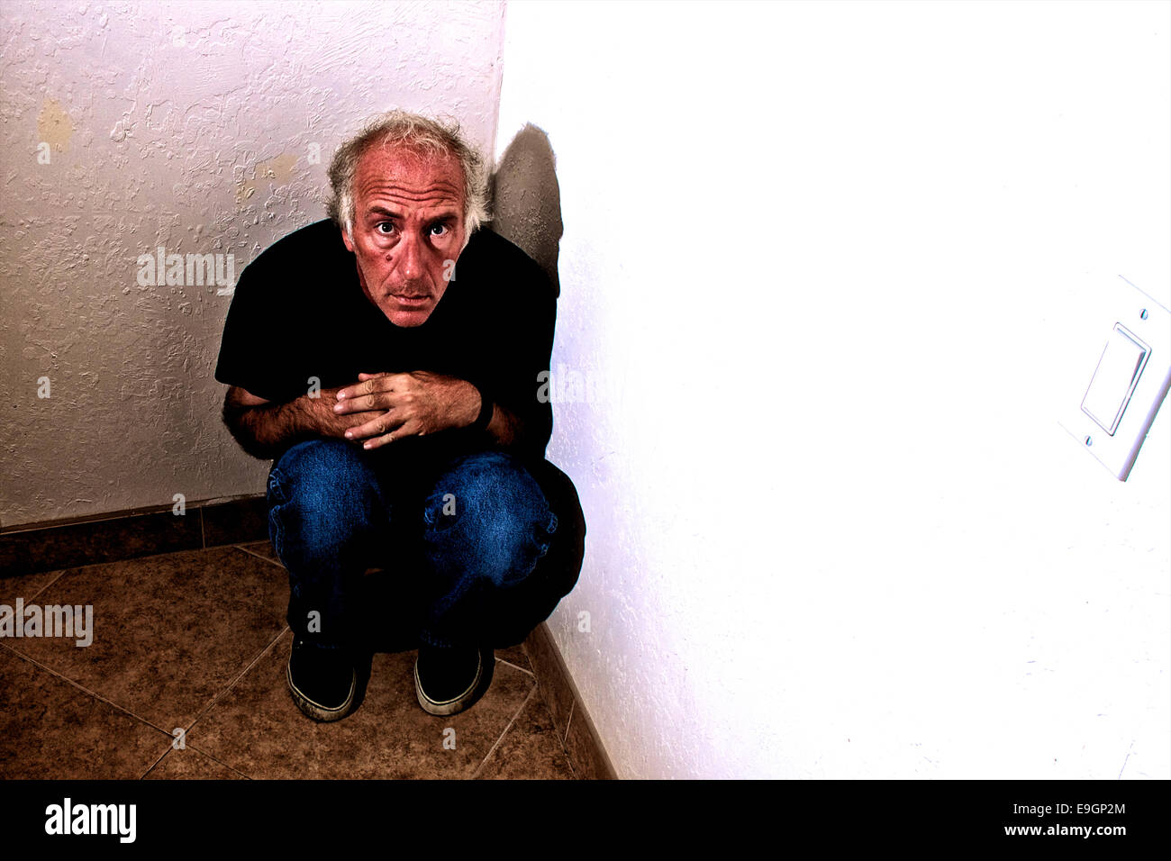 An older white man is crouched down in a corner looking up fearfully at viewer. - Stock Image
