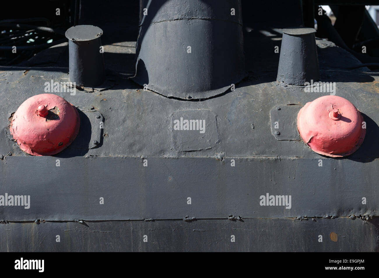 Closeup view of some metallic details of an old steam locomotive. Black and red colors of an iron construction - Stock Image