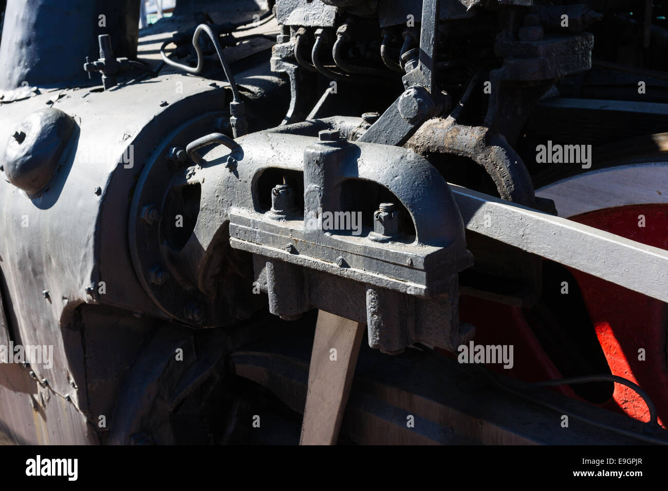 View of the piston mechanism of an old steam locomotive. Black metal and red wheel - Stock Image