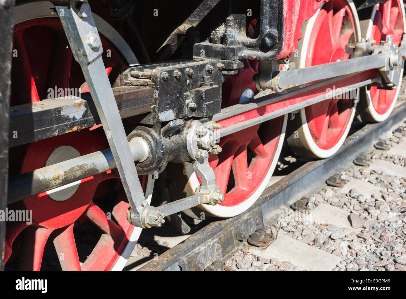 Closeup view of steam locomotive wheels, drives, rods, links and other mechanical details. White, black and red - Stock Image