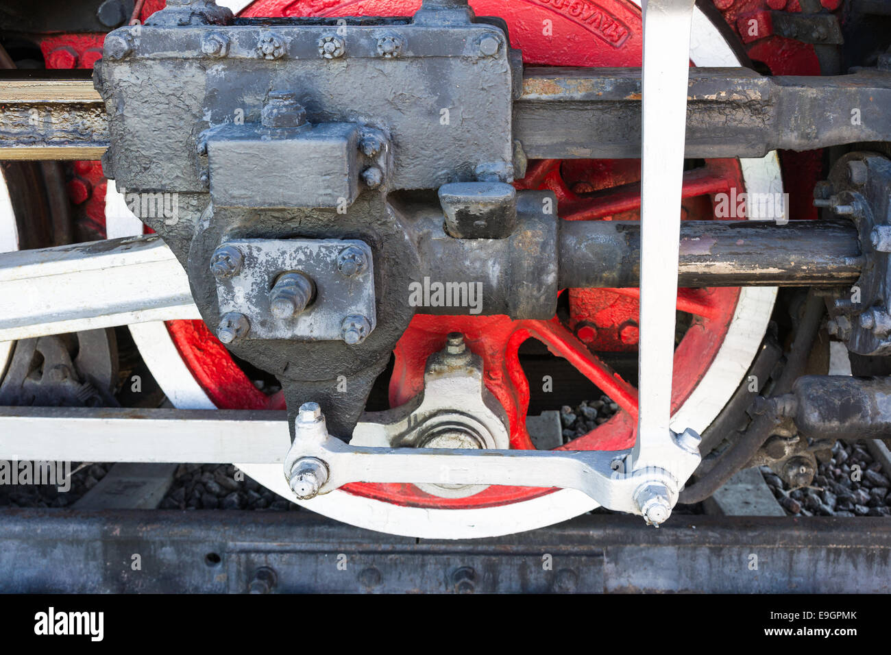 Closeup view of steam locomotive wheels, drives, rods, links and other mechanical details. White, black and red Stock Photo