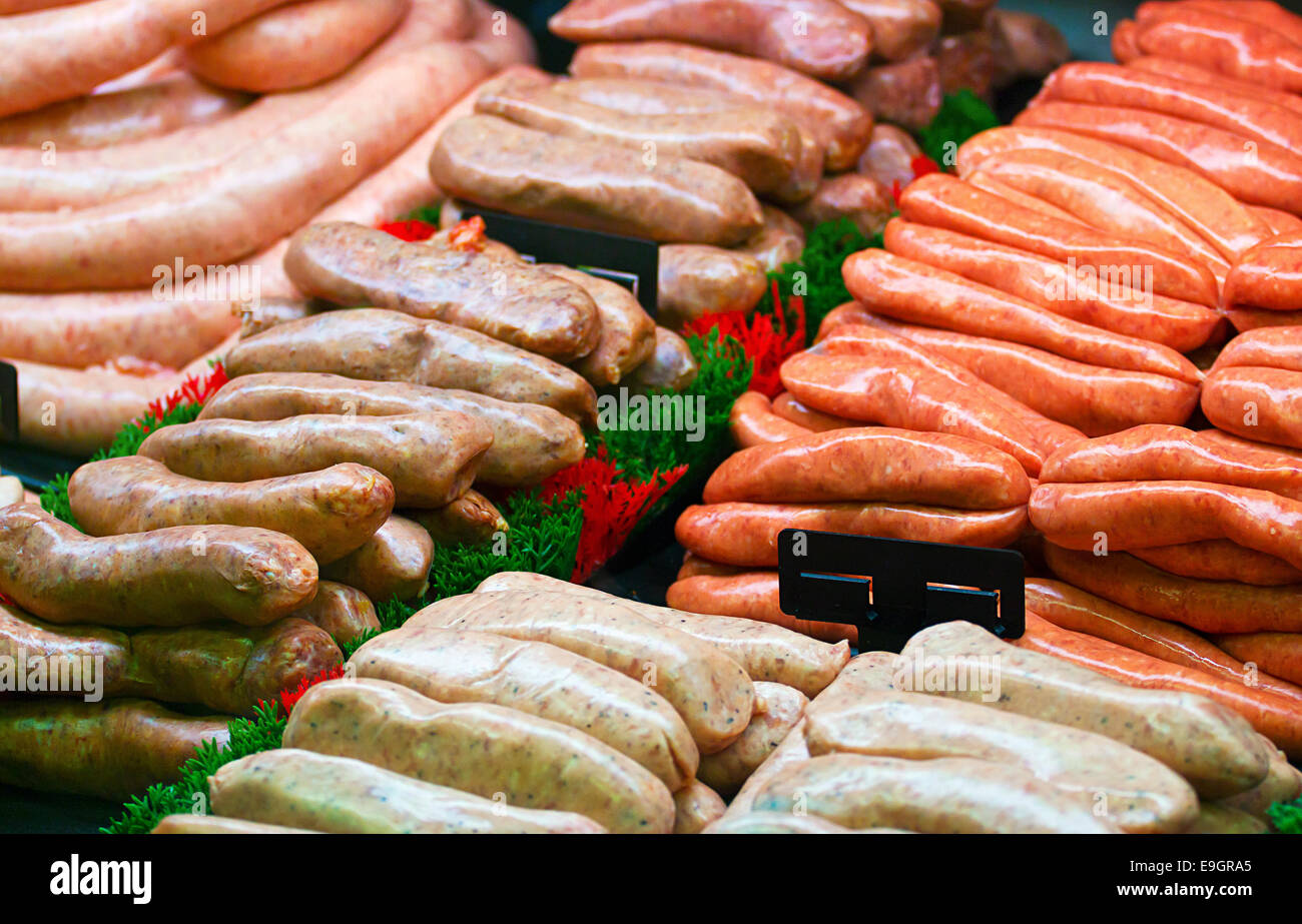 Selection of speciality sausages on display at a butchers counter or delicatessen window - Stock Image