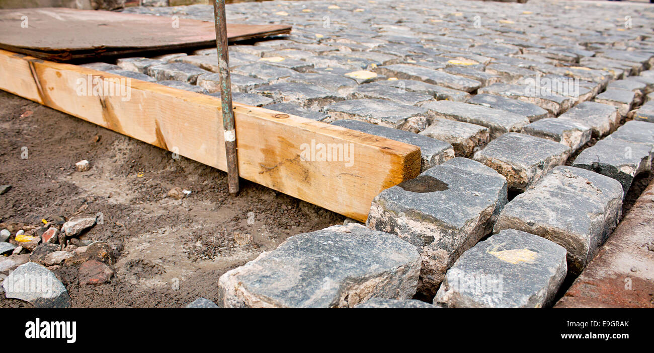Traditional Cobble stone paving being layed by building contactor - Stock Image