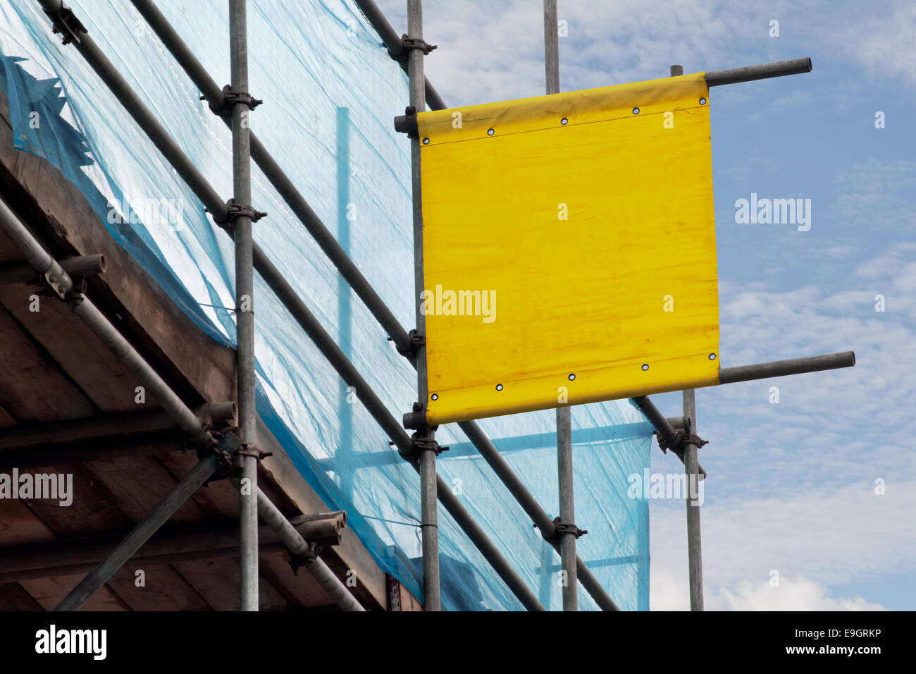 Blank scoffolding sign for advertising a scaffolders business erected on some scaffold a prime vantage point for - Stock Image