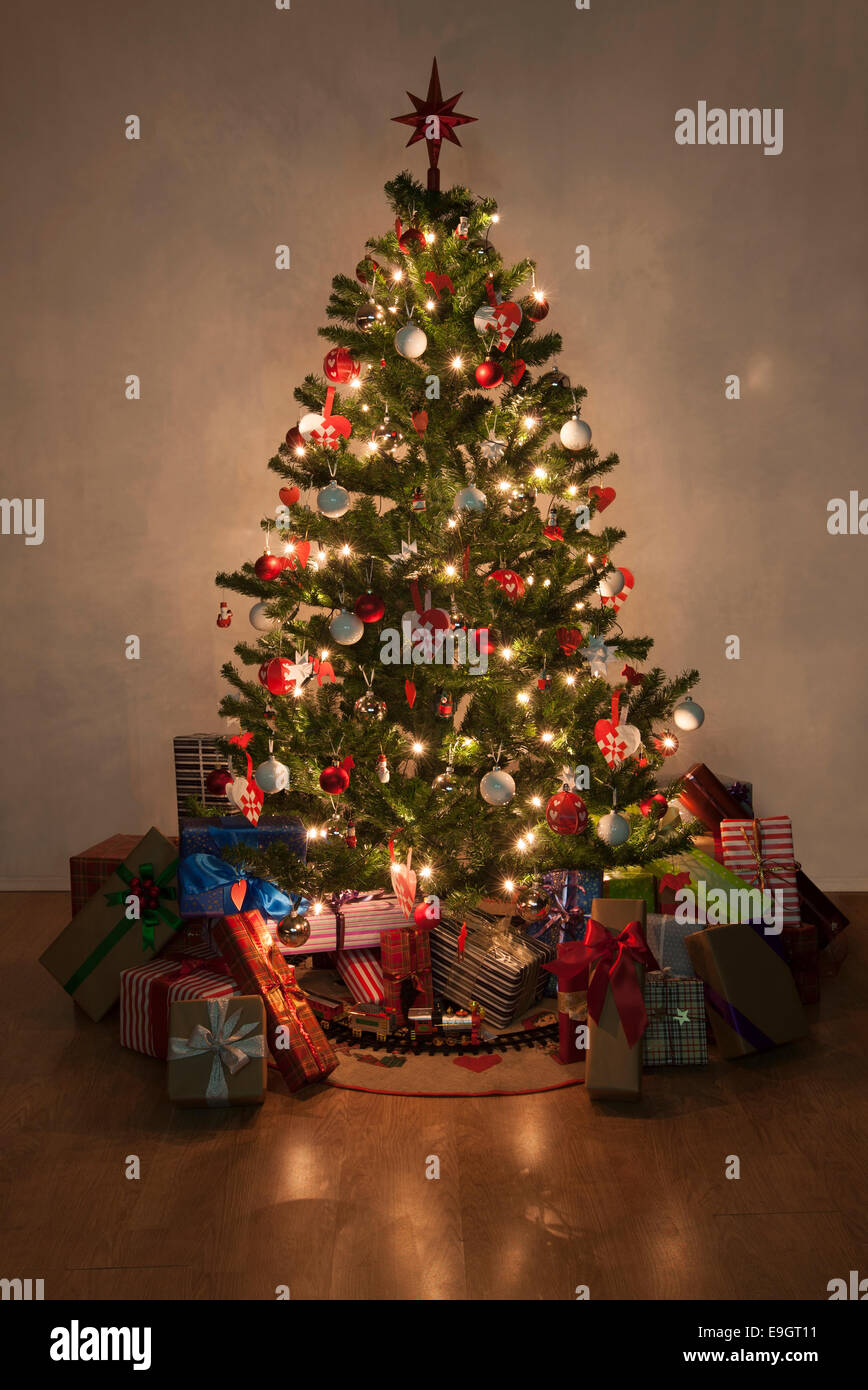 Beautiful christmas tree with lights and presents - Stock Image