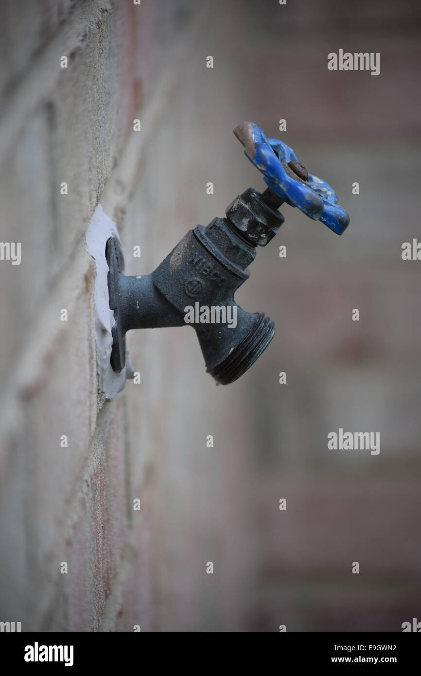Water spigot on the side of a house - Stock Image