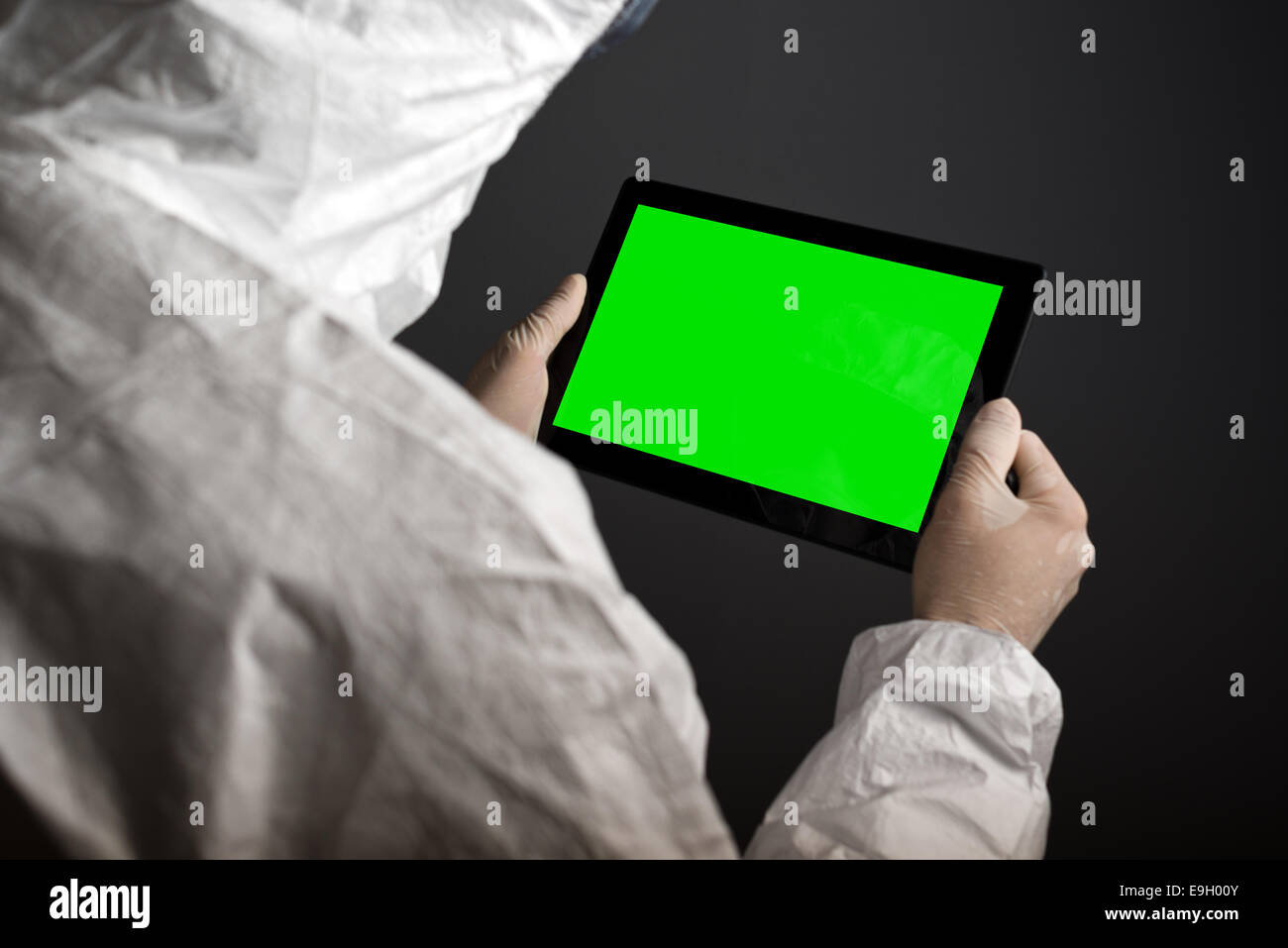 Chemist holding digital tablet with blank green screen. - Stock Image