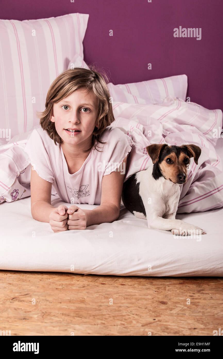 Girl lying in bed with a Danish Swedish Farmdog Stock Photo