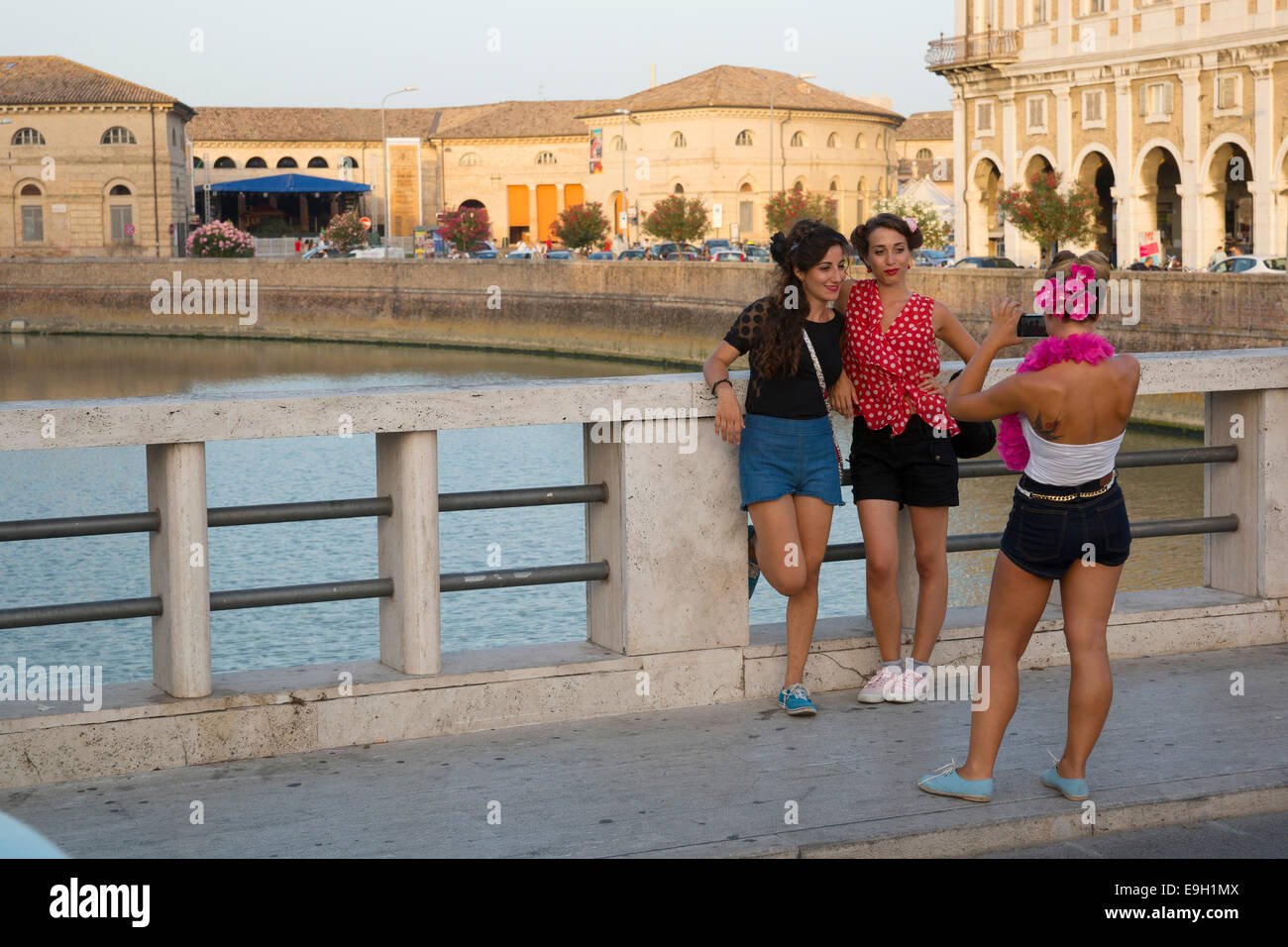 Women posing on the bridge crossing the Nevole River during the Summer Jamboree Rock'n'Roll Festival, historic - Stock Image