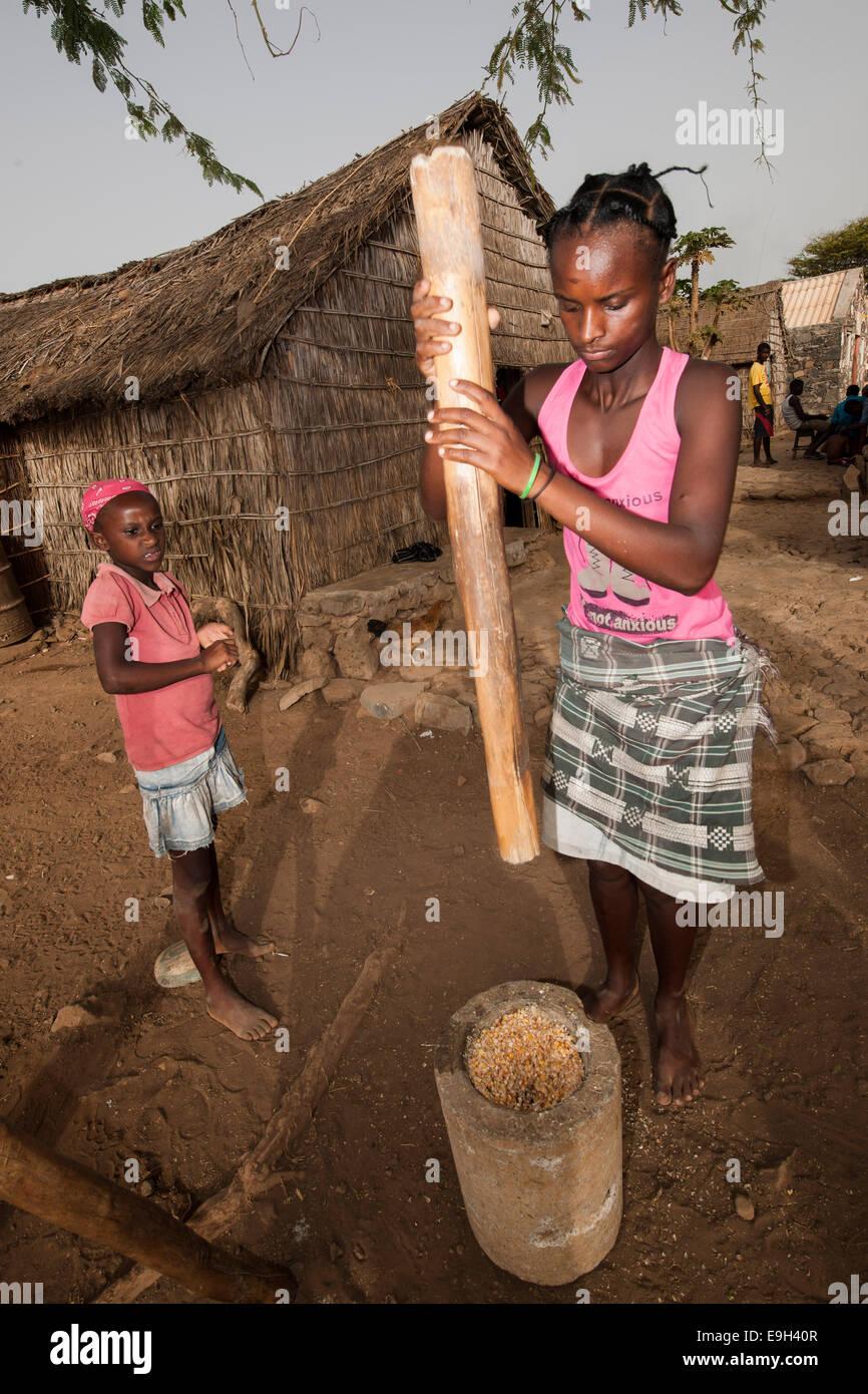 Women of the Rabelados religious community pounding corn in a mortar, near Tarrafal, Santiago, Cape Verde - Stock Image
