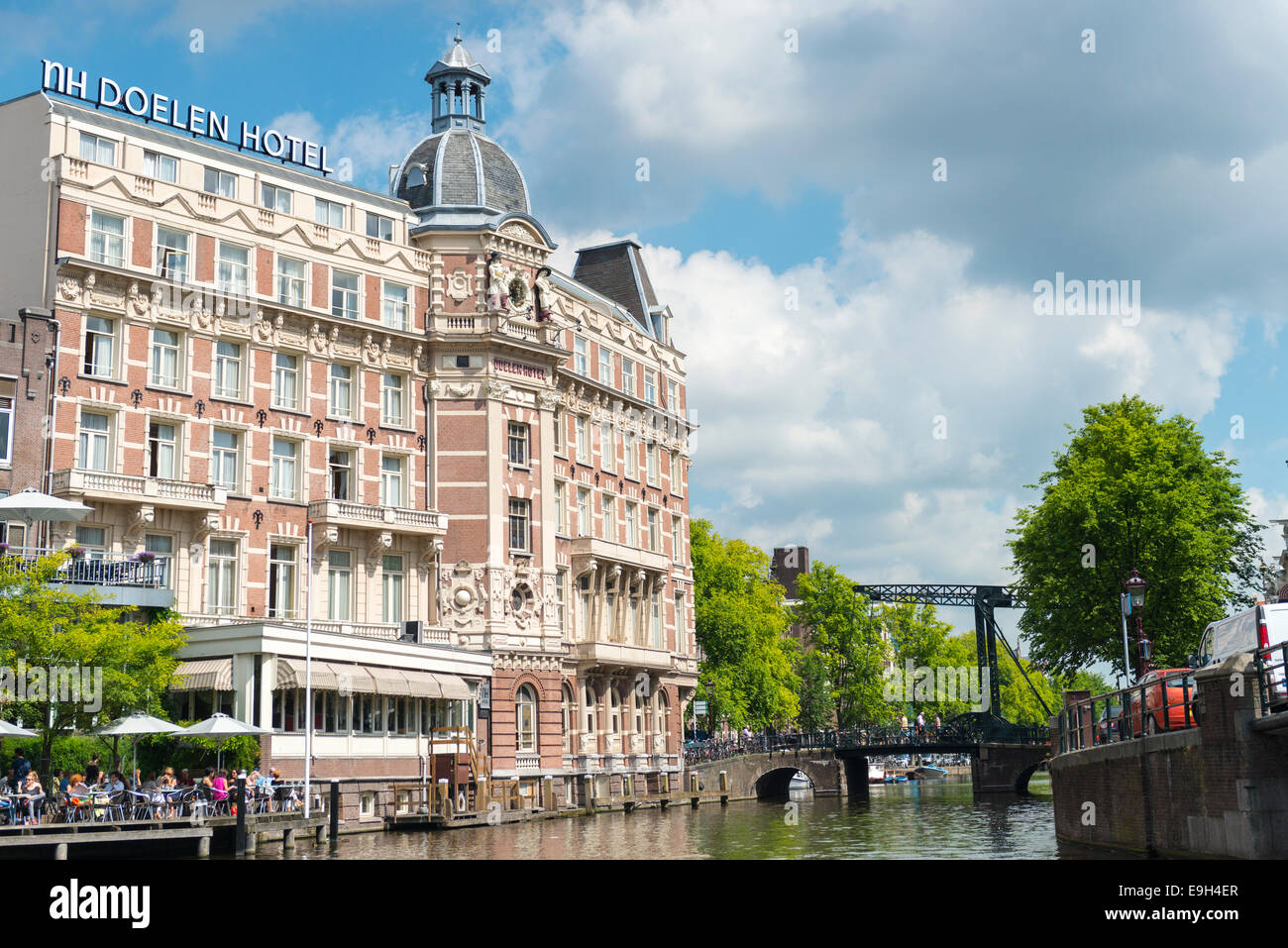 Doelen Hotel and gracht with guests on a terrace, Amsterdam, Netherlands - Stock Image