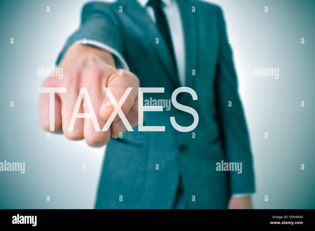 man wearing a suit pointing the finger to the word taxes written in the foreground - Stock Image
