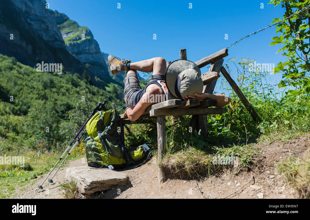 Female hiker lying on a bench, Champéry, Canton of Valais, Switzerland - Stock Image