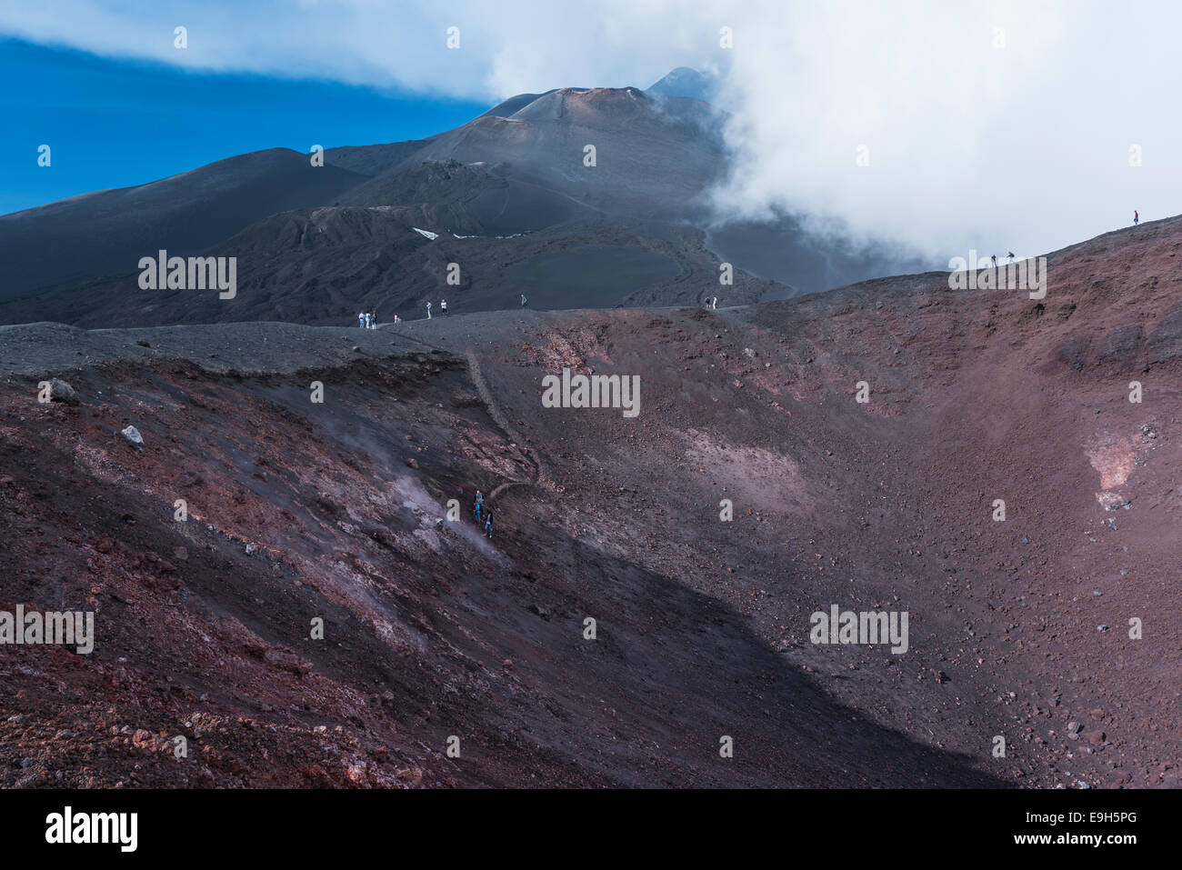 Tourists on the La Montagnola crater, lava fields behind, south side, Mount Etna in Zafferana, Sicily, Italy - Stock Image