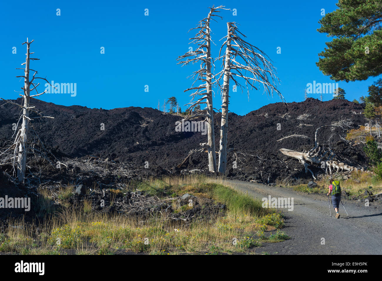Hiker on the gravel road through the lava field from 2002, Mount Etna, in Mascali, Sicily, Italy Stock Photo