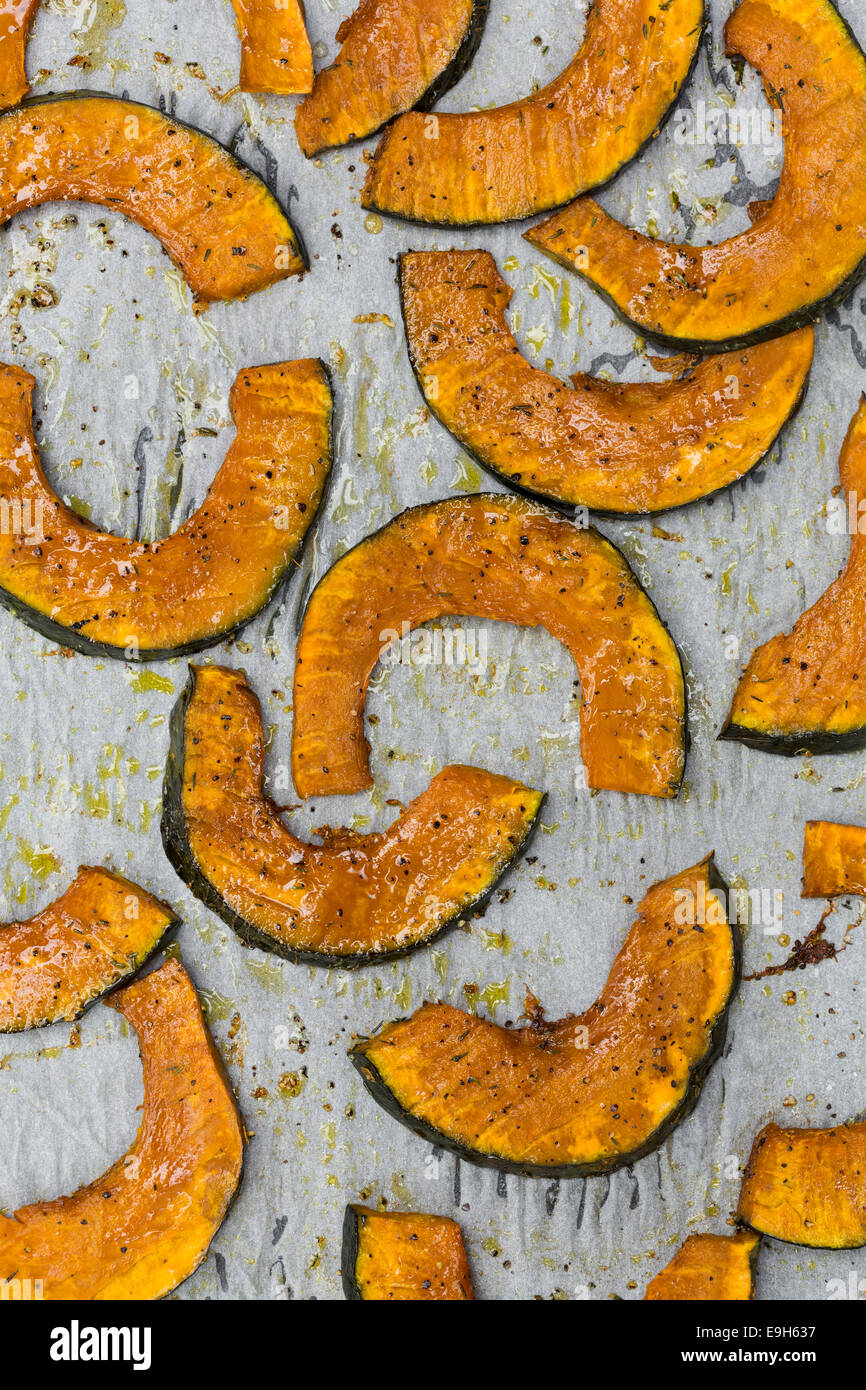 Roasted slices of pumpkin on a baking tray - Stock Image