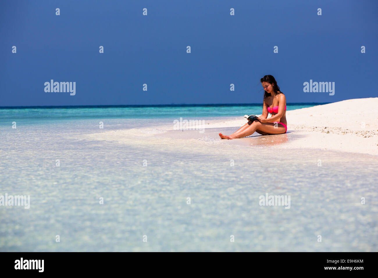 Woman with a book sitting on the beach, Male, North Male Atoll, Maldives - Stock Image