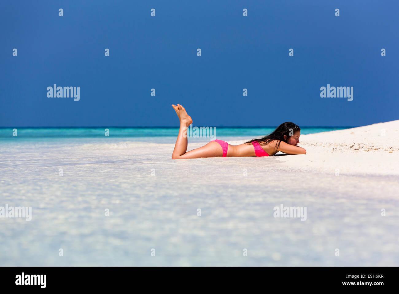 Woman in a pink bikini lying on the beach, Male, North Male Atoll, Maldives - Stock Image