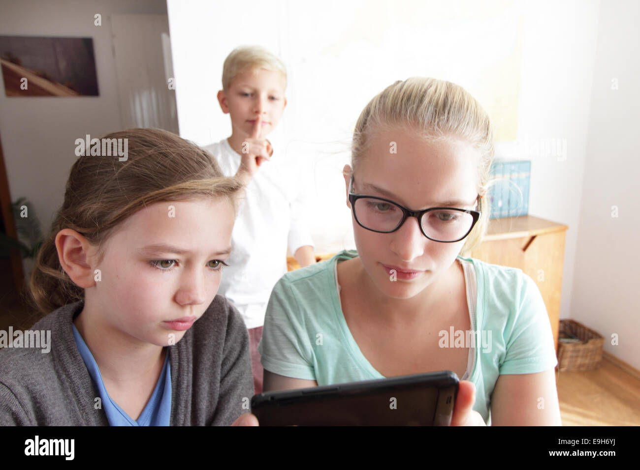 Girls with a smartphone, boy watching them, Baden-Wuerttemberg, Germany - Stock Image
