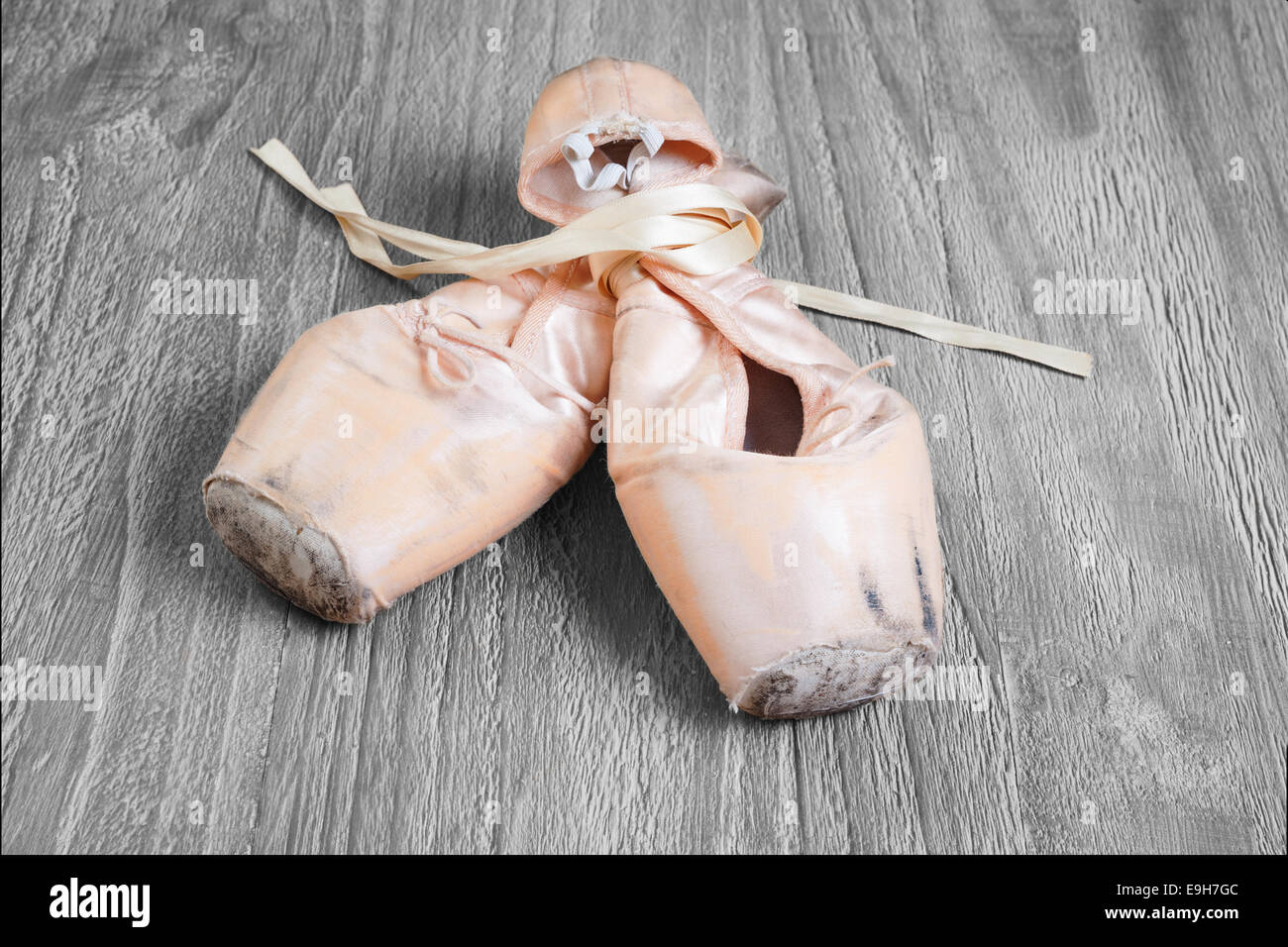 Old used  ballet pointe shoes on vintage wooden background - Stock Image