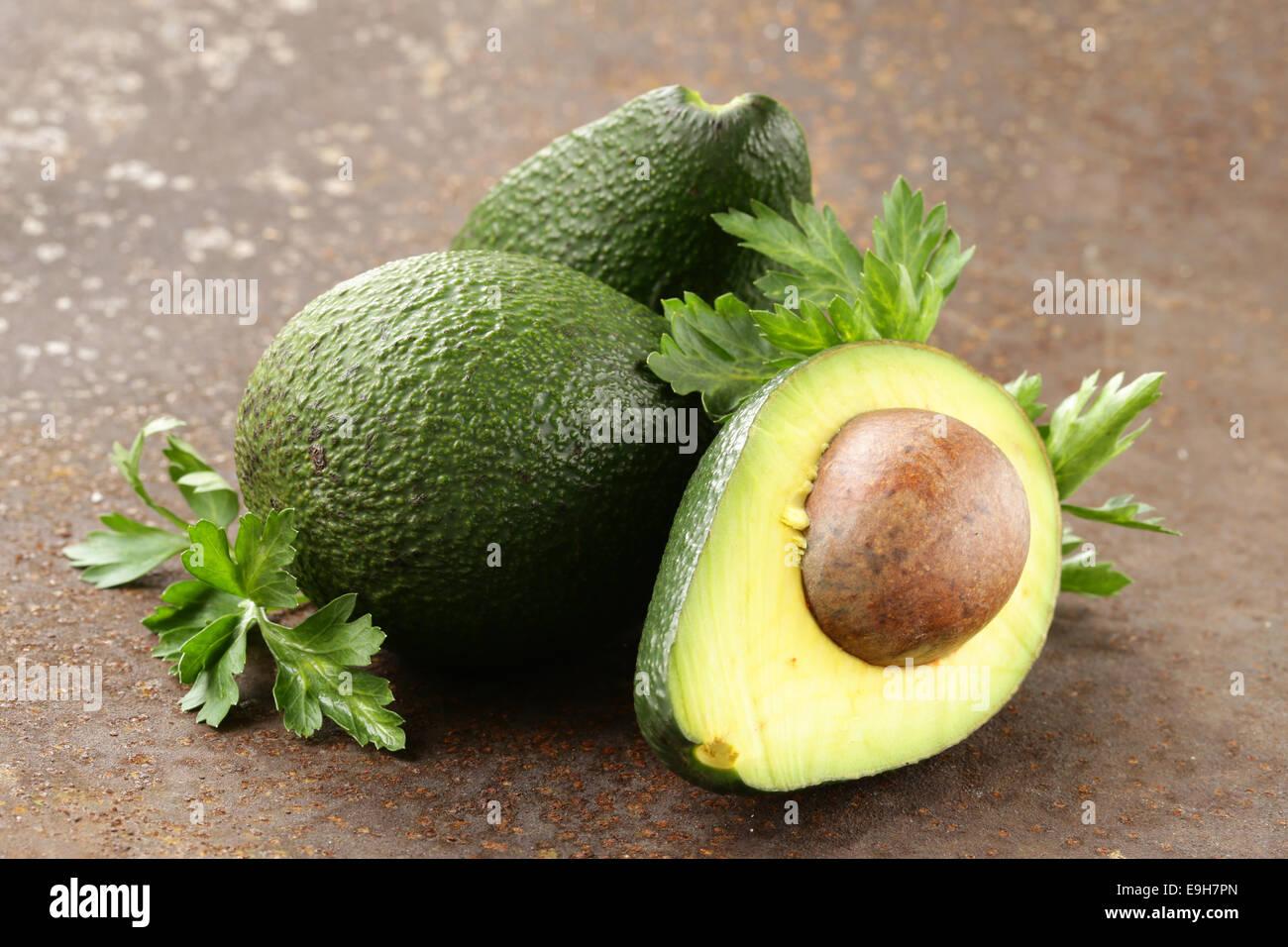 fresh organic ripe avocado with leaves of parsley - Stock Image