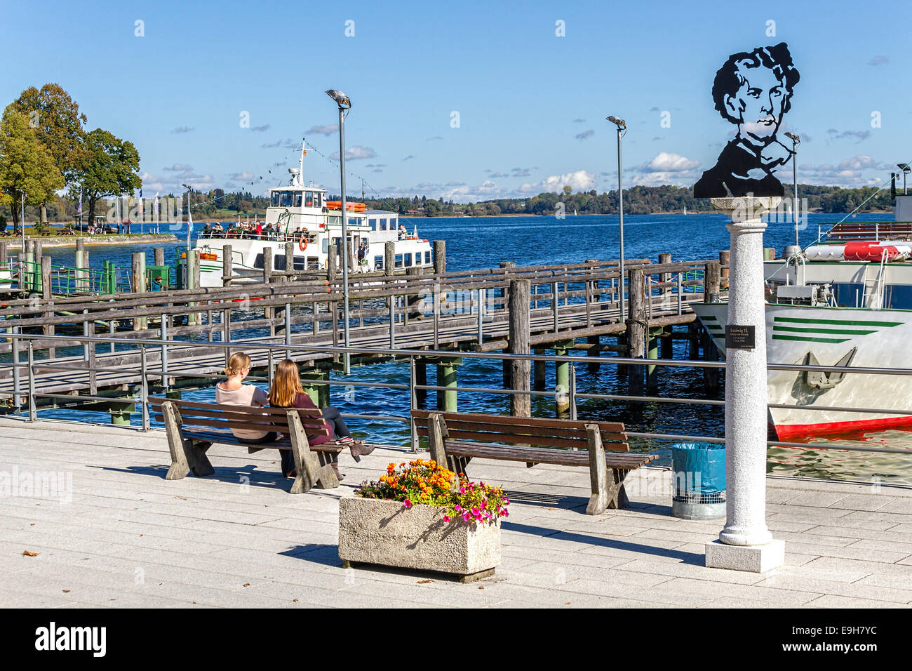 2 people sitting on bench seat at Boat Harbour, Prien Stock, Chiemsee, Chiemgau, Upper Bavaria , Germany, Europe. Stock Photo