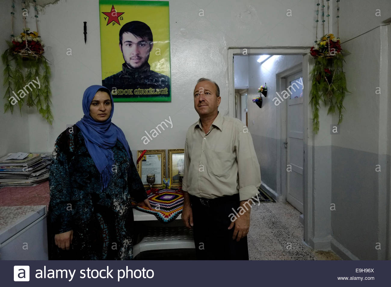 Bereaved parents of a Kurdish People's Protection Unit YPG fighter killed by ISIS or ISIL posing with his photograph - Stock Image