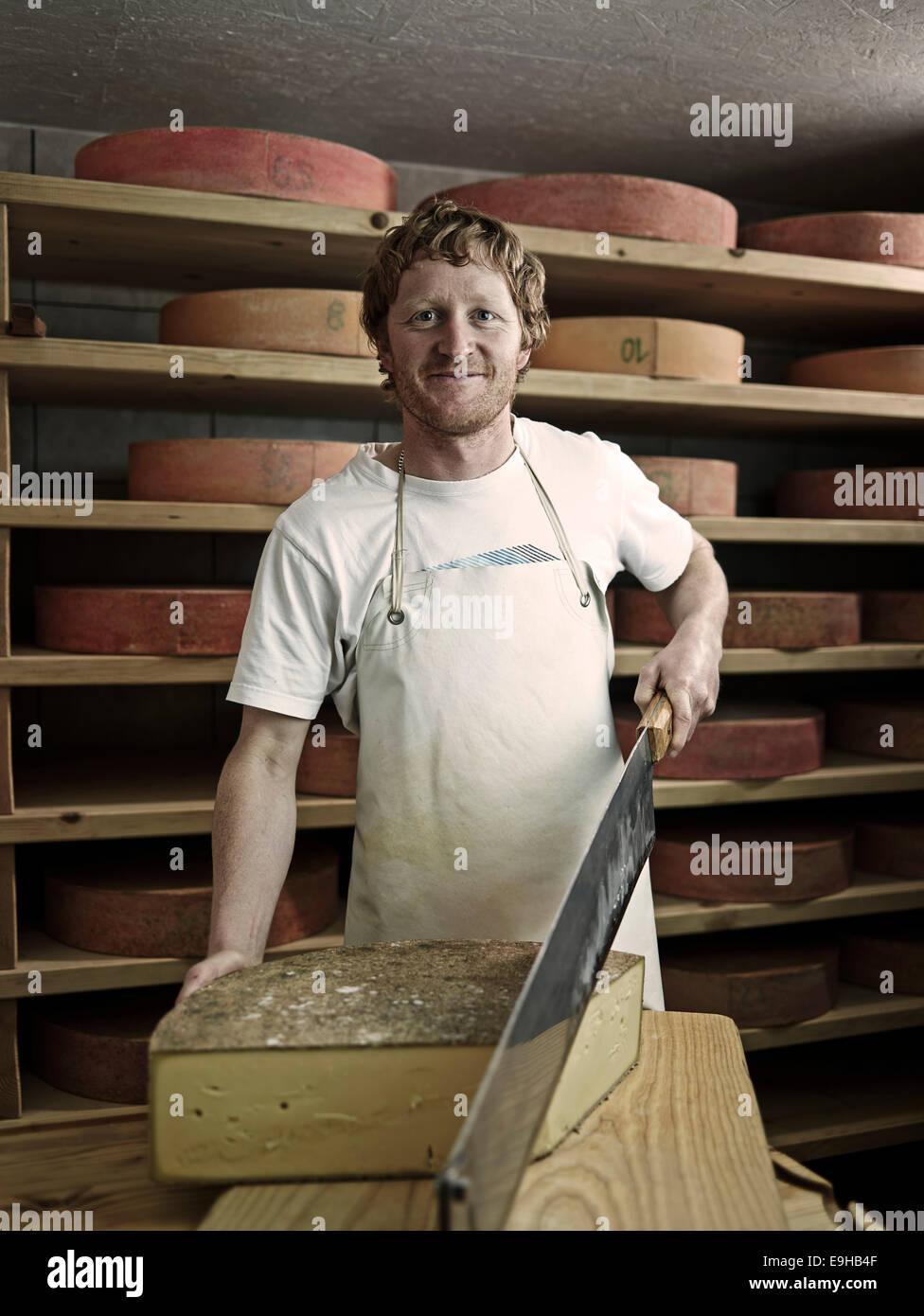 Dairyman cutting a mountain cheese, Steinbergalm, Inneralpbach, Alpbach, Tyrol, Austria Stock Photo