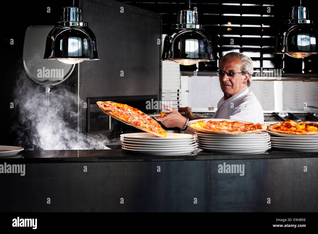 Pizza baker taking the finished pizza out of the oven with a pizza shovel - Stock Image