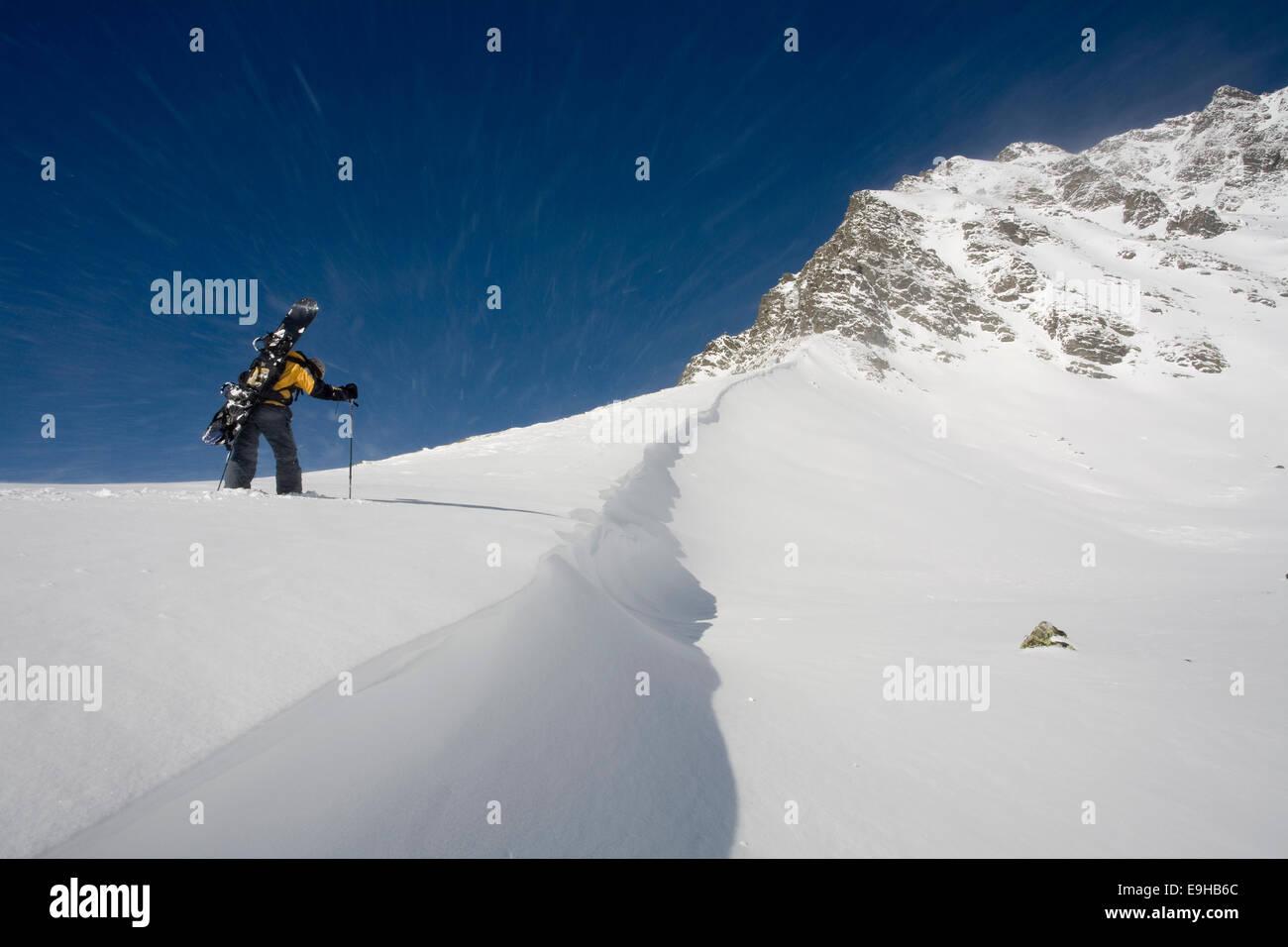 Snowboarder, freerider, during the ascent, near Kühtai, Tyrol, Austria - Stock Image