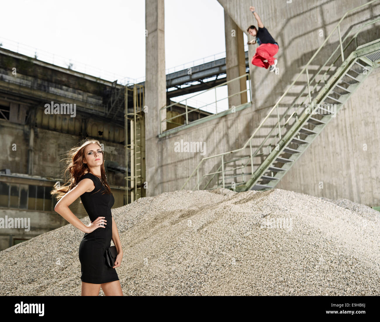 Young woman in black dress standing in front of a cement plant, young man jumping from a railing, Kiefersfelden, - Stock Image
