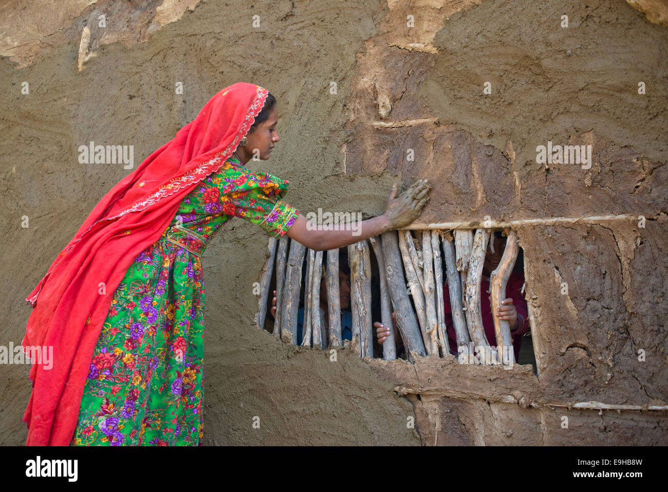 Girl in traditional dress plastering the wall of a house with a mixture of water, sand and cow dung, Rann of Kutch, - Stock Image